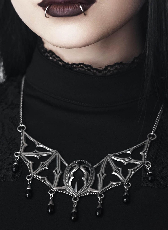 Killstar halsband. Vingar med gotiska detaljer och små hängande svarta glasdroppar. Justerbar kedja. Tillverkad i silverfärgad metall. Storlek: Hängsmycke 12cm, Kedja 30cm
